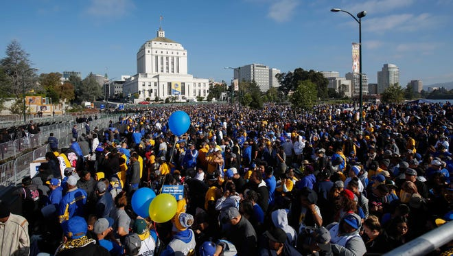 Fans gather before the Warriors NBA championship celebration in Oakland, Calif.