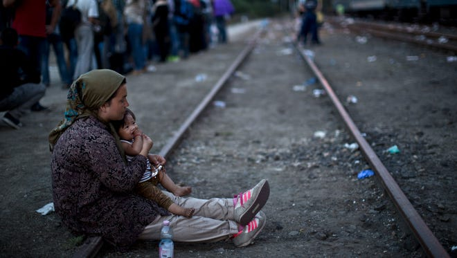An Afghan refugee woman holding her daughter rests while waiting to board a train heading to the Austrian border, in Roszke, southern Hungary, Monday, Sept. 14, 2015.