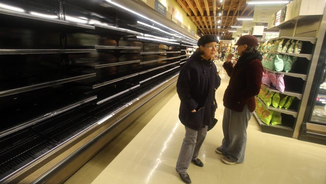 Customers stand in front empty shelves at the Mrs. Green's grocery in Rye on Tuesday, Nov. 15, 2016.