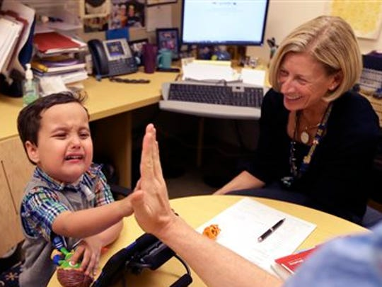 Grant Hasse cries as he receives a high-five from Dr. Glenn Green, a pediatric airway surgeon at the University of Michigan's C.S. Mott Children's Hospital.. Grant, 3, was born with two very rare conditions.