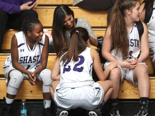 Assistant girls basketball coach Jordan Hansen, center, talks with team members Rickii Bennett, from left, Meriah Romero and Isabelle Smith before a game at the school. Hansen is a former player on the team.