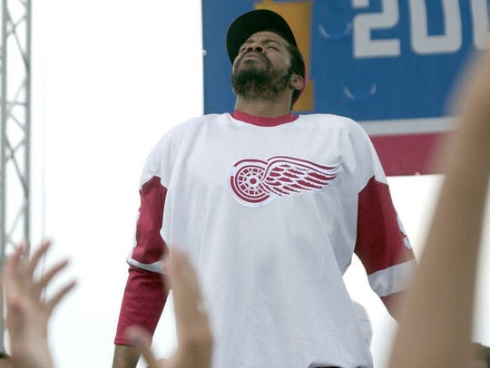 Rasheed Wallace, wearing a Detroit Red Wings jersey, reacts to the crowd's applause during a Detroit Pistons rally after the team's victory parade,  June 17, 2004, in Detroit.