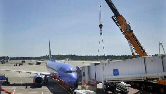 Workers use a crane to lift a jetway, at right, away from a Southwest Airlines airplane after the jetway suffered a mechanical failure on May 13, 2014, at Seattle-Tacoma International Airport.