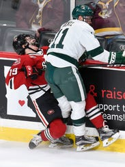 St. Cloud State's Mikey Eyssimount,19, gets checked