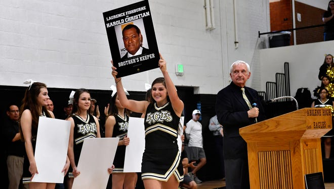"""Producer Mark Smith on Wednesday watches as Abilene High School cheerleader Givan Walker carries a placard announcing Laurence Fishburne's role in an upcoming movie about the 2009 Eagles football championship. The movie, """"Brother's Keeper"""", will feature Fishburne as the late Harold Christian, who owned the well-regarded Harold's Pit Bar-B-Que."""