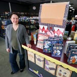 Camille Jones, the co-owner of Borderlands Games, holds popular board game Settlers of Catan inside the shop. The store is celebrating its 20th anniversary in Salem.