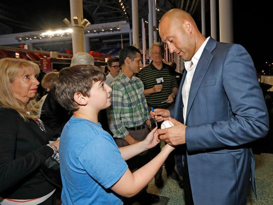 Miami Marlins co-owner Derek Jeter gives an autograph to a fan after a town hall meeting at Marlins Park in Sunrise, Fla., Tuesday, Dec. 19, 2017. (Al Diaz/Miami Herald via AP)
