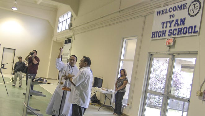 In this August 2014 file photo, Father Joel Alve sprinkles holy water as he conducts a blessing during the ribbon-cutting ceremony at Tiyan High School.