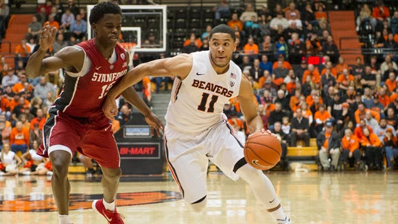 Oregon State guard Malcolm Duvivier (11) dribbles while defended by Stanford guard Marcus Allen (15) at Gill Coliseum on Jan. 6, 2016.