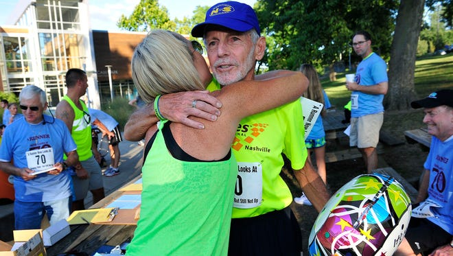 Peter Pressman gets a hug from Kellie Arrant on Aug. 12, 2015, at McCabe Community Center in Nashville. He celebrated his 70th birthday with others at a community fun run/walk.