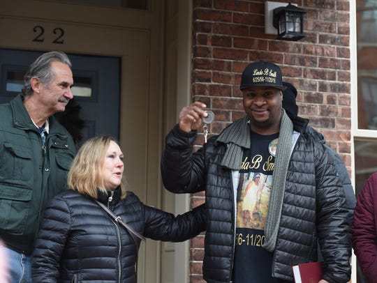 Keith Smith, right, waves the keys to his family's