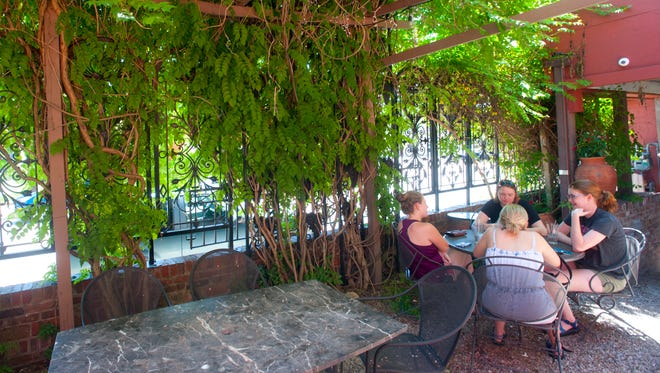Patrons eat under a grape arbor in the outdoor dining area of the Grape Leaf restaurant on Frankfort Ave.