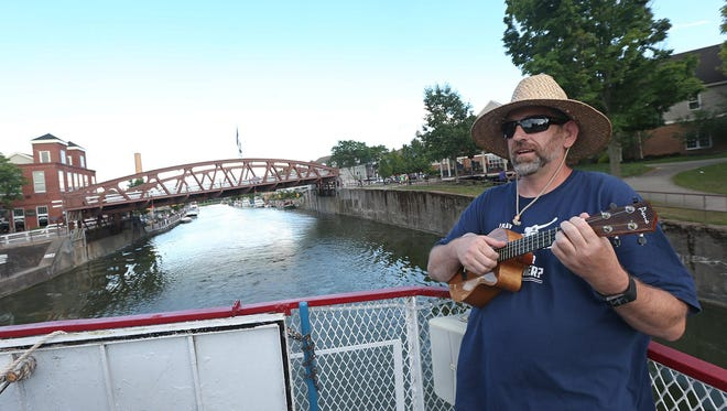 Michael Overman of Fairport plays on his ukelele as the village of Fairport recedes behind him during a ukelele jam cruise on the Colonial Belle as it sailed on the Erie Canal on Aug. 3, 2015.