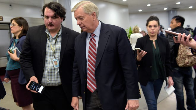 Sen. Lindsey Graham, R-S.C., center, speaks to reporters following a briefing on Syria on Capitol Hill in Washington, Friday, April 7, 2017. Amid measured support for the U.S. cruise missile attack on a Syrian air base, some vocal Republicans and Democrats are reprimanding the White House for launching the strike without first getting congressional approval. (AP Photo/Susan Walsh)