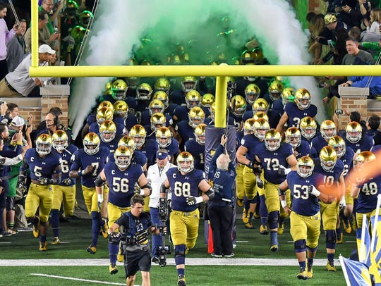 Notre Dame players run out of the tunnel before their