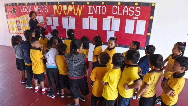 A teacher uses the roster posted on a bulletin board to double-check the students enrolled in her class, during their first day back to school, at Chief Brodie Memorial Elementary School in Tamuning on Thursday, Aug. 17, 2017.