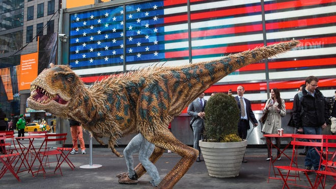 """This image released by Boneau/Bryan-Brown shows a man in a baby Tyrannosaurus Rex costume in Times Square on March 20, 2014, in New York to promote """"Walking with Dinosaurs, the Arena Spectacular."""" The show is coming back to the U.S. and Canada for the first time since 2007, and many of its lifelike puppets will be wearing downy feathers, reflecting recent discoveries."""