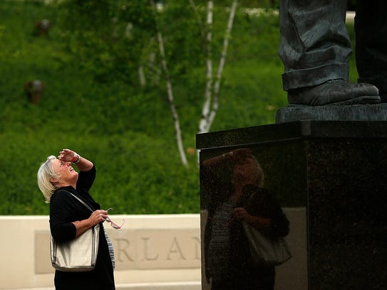 A woman looks up at the Vince Lombardi statue at Lambeau