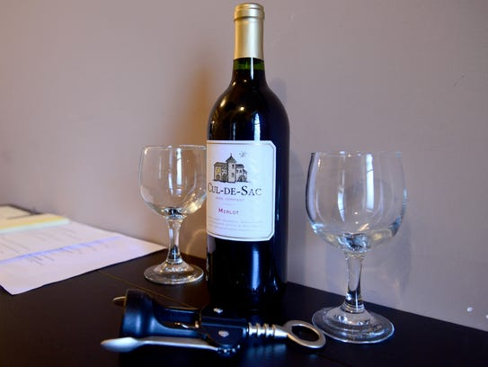 A bottle of wine sits on the table of the back entrance