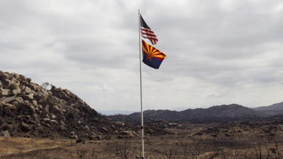 Flags fly in tribute, near the site where 19 hotshots died fighting the Yarnell Hill Fire.
