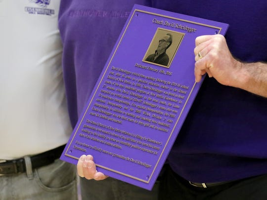 Former New Berlin Eisenhower Boys Basketball Coach David Scheidegger holds a cast plaque as he is photographed with family during a ceremony to rename the school's Upper Gym for the Coach Scheidegger on Feb. 16. During his 27 years as coach, Scheidegger's teams compiled a record of 430-187 and the 2008 Wisconsin Division 2 State championship.