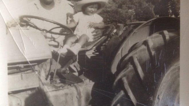 Marie Lopez Rogers rides on a tractor with her father, Martin R. Lopez, a farm worker in Avondale, in the early 1950s.
