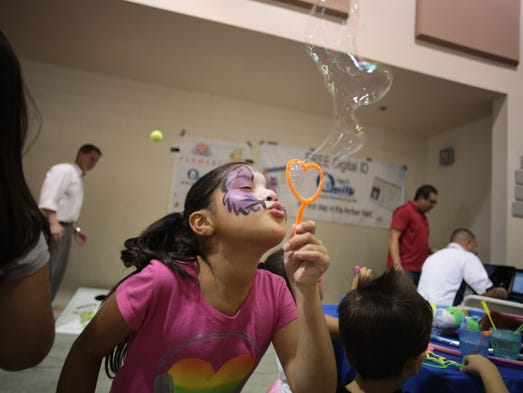Giovanna Garica blows bubbles during fundraiser for Desirae Cechin who has stage 4 high-risk neuroblastoma, which affects the nervous system. So far, $200,000 of the $300,000 has been raised for her treatment. Photo taken on Saturday, July 26, 2014 at the Riverside County Fairgrounds in Indio.