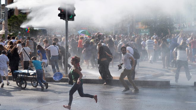 Turkish riot police water cannon vehicles disperse marchers gathered for the 13th annual Gay Pride Parade in Istanbul on June 28, 2015.