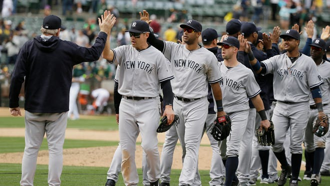 The New York Yankees celebrate at the end of a baseball game against the Oakland Athletics, Sunday, May 22, 2016, in Oakland, Calif.