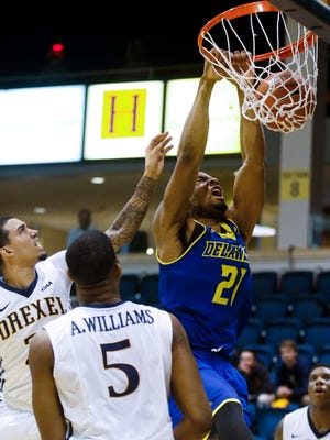 Delaware's Marvin King-Davis get a late jam in front of Drexel's Samy Mojica in the second half of the Blue Hens' 74-64 loss at the Daskalakis Athletic Center in Philadelphia, Pa.