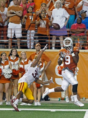 Texas receiver John Harris (9) catches a pass against Iowa State's Nigel Tribune (34) near the end of Saturday's game.