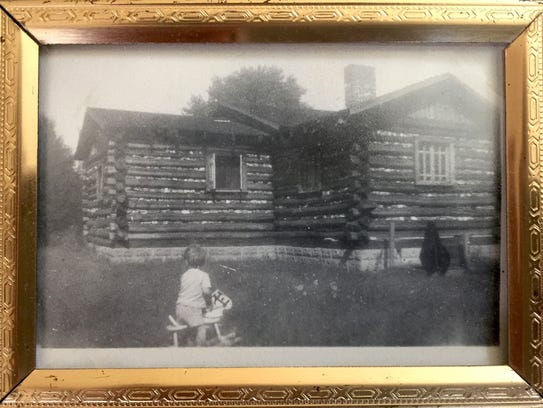 As a child, Tom sits in front of his family's log cabin.