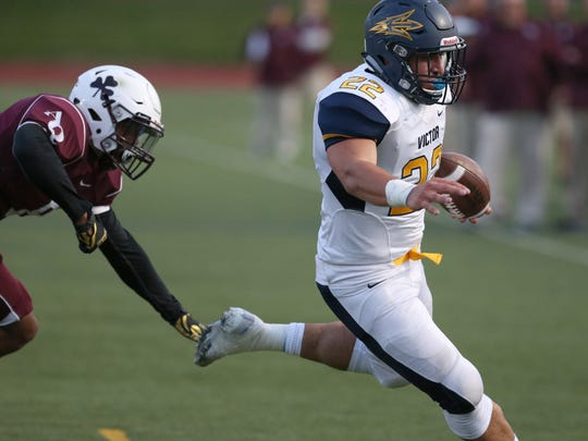 Victor's Chris Varone, right, scores the first touchdown of the game as he runs wide around Aquinas' Shane Noble Jr..