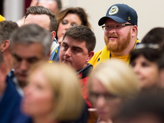 Soccer fans listen to council members speak before