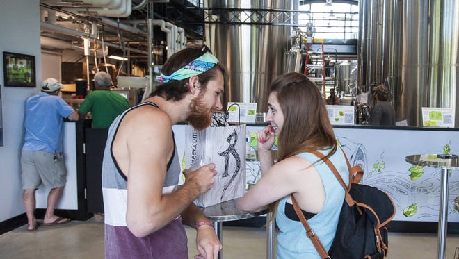 Patrick Thompson, left, and Kate Bradley of Somerville, Massachusetts, sample some beer during the opening of the new The Alchemist brewery in Stowe on Thursday, June 30, 2016.