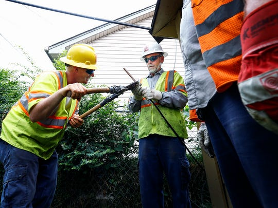 Davis H. Elliot Construction electricians Jonathan Turner (left) and Paul Perkins (right) of Lexington, Ky., work on crimping an electrical line behind homes on University near Vollintine Thursday afternoon.