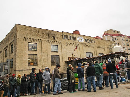 The line wraps around the side of the Lakefront Brewery building during a Black Friday special release.