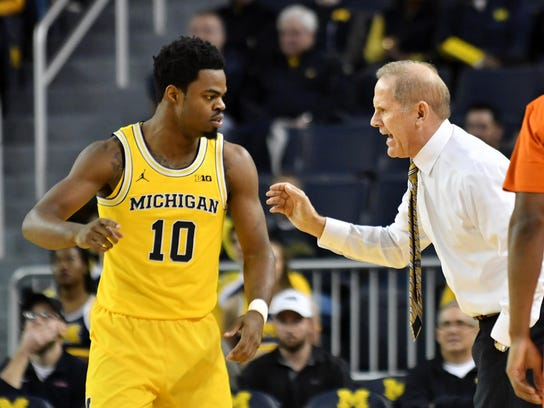 Michigan coach John Beilein talks with guard Derrick