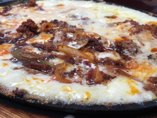 Queso Fundido, a sizzling plate of melted cheese topped with sautéed onion chorizo.