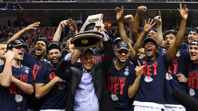 Gonzaga Bulldogs head coach Mark Few raises the trophy marking the West Region title