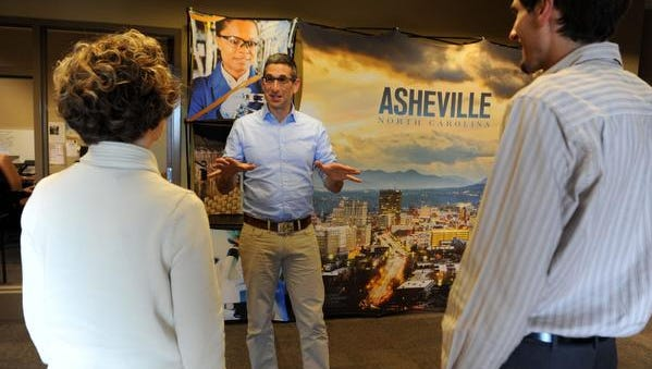 Josh Dorfman talks with colleagues in the economic development office of the Asheville Chamber of Commerce Wednesday afternoon Oct. 22, 2014.