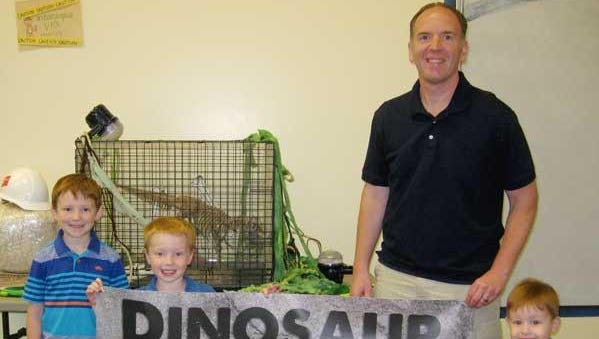 Joe Mand of Lakeside Evening Kiwanis displays the Dinosaur Family Night banner with his children (from left) Jack, Carter and Eli in anticipation of the Children's Museum of Fond du Lac's Dinosaur Family Night on Friday, June 19.