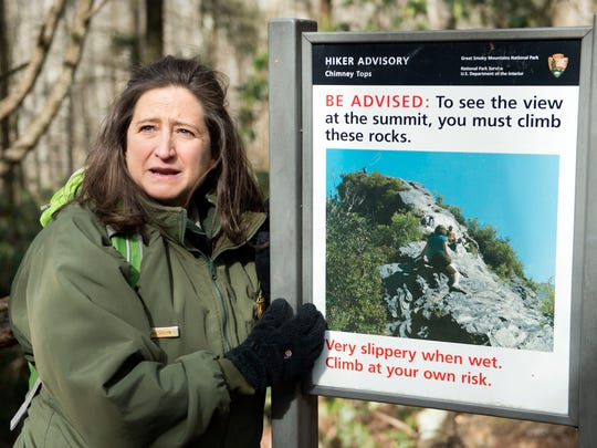 Great Smoky Mountains National Park Spokesperson Dana Soehn points to a sign with a photo of Chimney Tops trail before the November wildfire damage took place, at the start of the trail Thursday, Feb. 16, 2017.