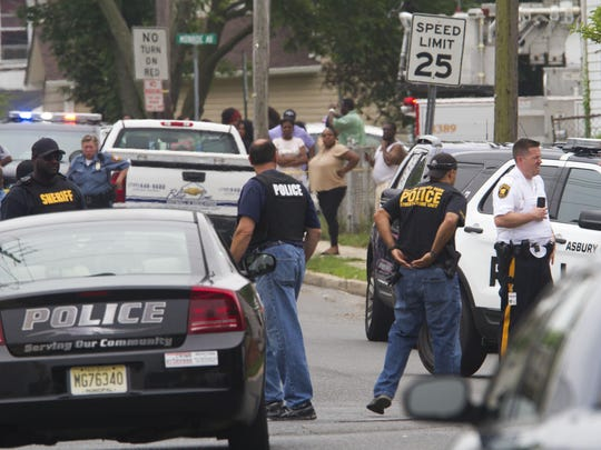 Police gather at the scene of a shooting in Asbury Park last week in which off-duty Neptune Police Sgt. Philip Seidle was charged with killing his wife.