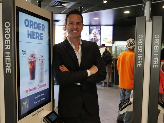 McDonald's franchisee Nick Karavites poses for a portrait at a self-service kiosk as a customer places an order at one of Karavites' restaurants in Chicago. The company that helped define fast food is making supersized efforts to reverse its fading popularity and catch up to a landscape that has evolved around it. That includes expanding delivery, digital ordering kiosks in restaurants, and rolling out an app that saves precious seconds.