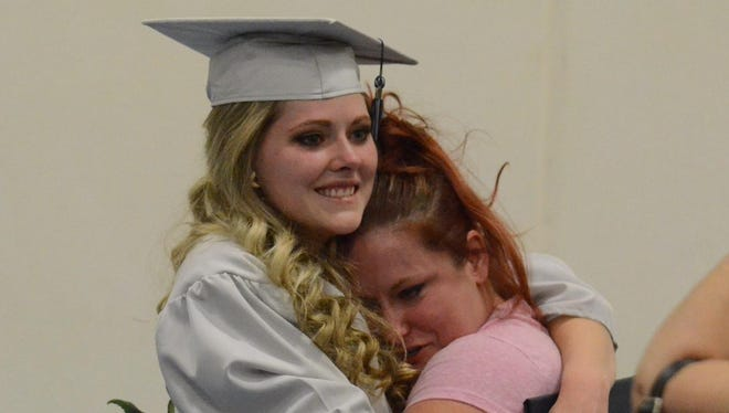SSHS graduate Mason Taylor hugs a friend as they pose for a photo after Thursday's Silver Stage High Commencement.