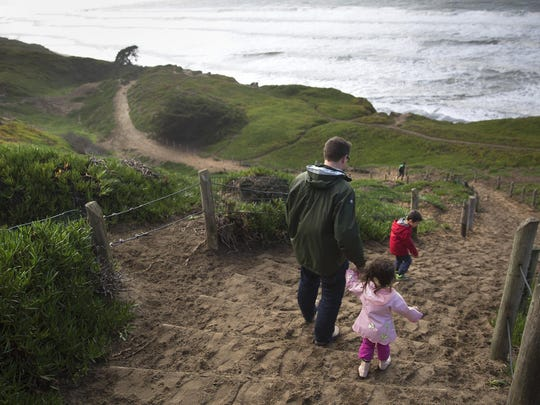 Visitors walk down the sand ladder to the beach at Fort Funston in the Golden Gate National Recreation Area in San Francisco.