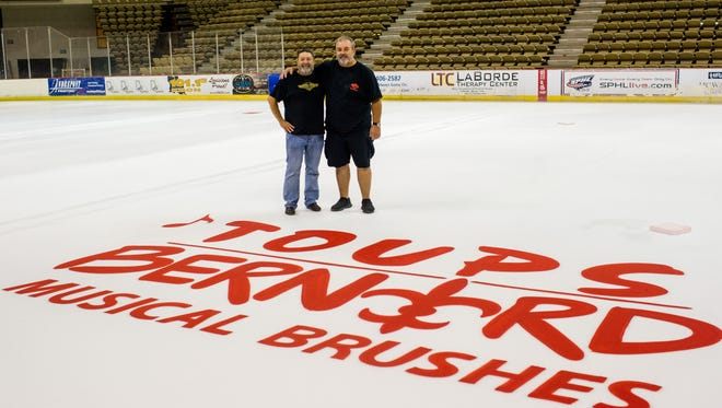 Musician Wayne Toups and artist Tony Bernard stand next to a painted logo for their new business at the Cajundome in Lafayette, La., Tuesday, Nov. 3, 2015. Toups and Bernard are starting a new business called Toups-Bernard Musical Brushes to sell their artwork and merchandise. The business' logo will be displayed on the hockey ice throughout the Louisiana IceGators' season.