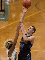 Castle's Alex Hemenway (12) makes a layup as the Reitz Panthers take on the Castle Knights at Reitz High School in Evansville, Ind., on Friday, Dec. 15, 2017. Castle won 71-53.