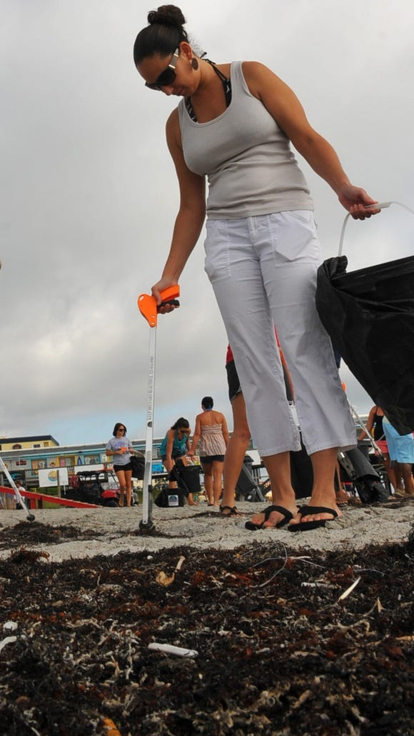 NASA employees and contractors help cleanup Cocoa Beach near the pier in this file photo. In this shot Zahyra Lebron painstakingly picks up cigarette butts.